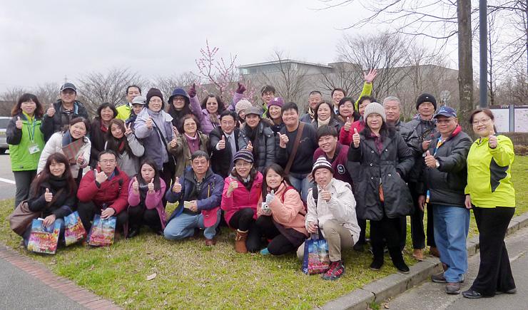 紅梅の前で職員と記念撮影する台湾からの観光客=チューリップ四季彩館