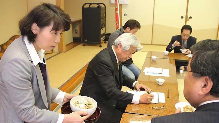 「フェンシング丼」を試食する研究会の会員らにこだわりを説明する坂井教諭(左)