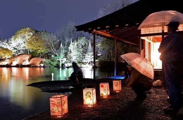 あんどんなどの明かりで幻想的な雰囲気に包まれた養浩館庭園=18日夜、福井市