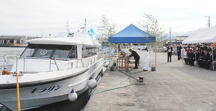 観光遊覧船の前で安全運航を祈願する関係者=滑川漁港
