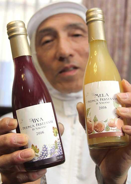 リンゴ果汁(右)と巨峰果汁の炭酸飲料を手にする野沢社長
