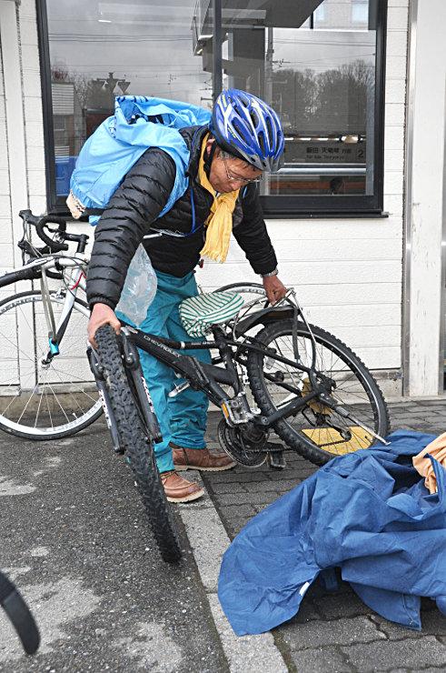 伊那北駅で電車を降り、運んできた自転車を袋から出す参加者