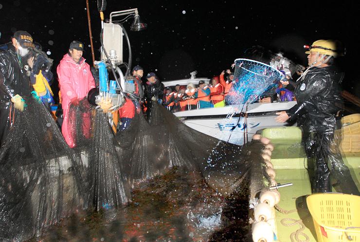 海上観光の開始を前に、ホタルイカ漁を観光船の上から間近で見る試乗会の招待客=19日午前3時48分、滑川沖