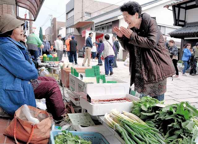 春分の日に合わせて再開し、出店者とお客の会話が弾んだ七間朝市=20日、福井県大野市の七間通り
