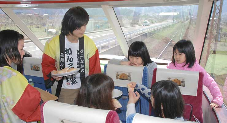 法被姿の高校生から中野市産のキノコを使ったスイーツを受け取る乗客