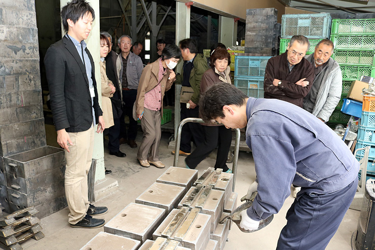 鋳型にスズを流し込む工程を見学する参加者=能作
