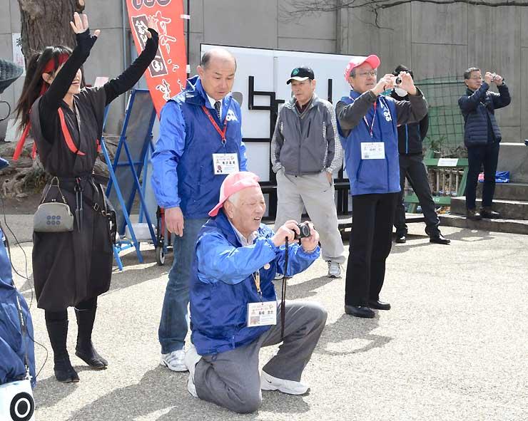 櫓門前で観光客を写真に収める「元祖シャッターマン」のメンバー