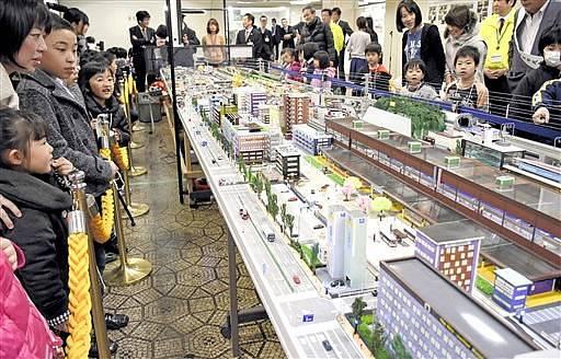 未来の北陸新幹線南越駅周辺などを舞台にした巨大ジオラマに見入る来場者=25日、福井県越前市生涯学習センター