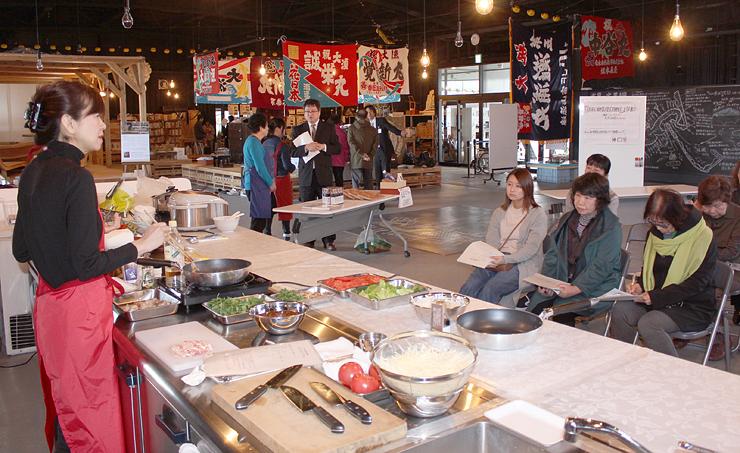 松井さん(左)の説明を聞く参加者=氷見市中央町、ひみ漁業交流館魚々座