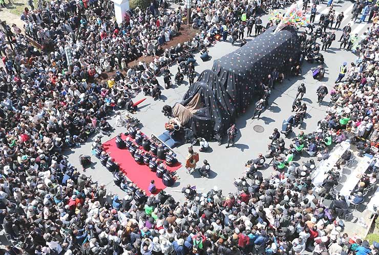 お練りまつりの最終日、多くの見物客が「東野大獅子」を取り囲んで見入った=27日午前11時50分、飯田市中央通り