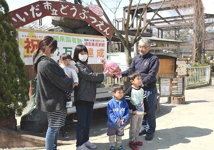 園長の長良さん(右)から来園者数14万人達成の記念品を贈られた奥山さんの家族=28日、飯田市