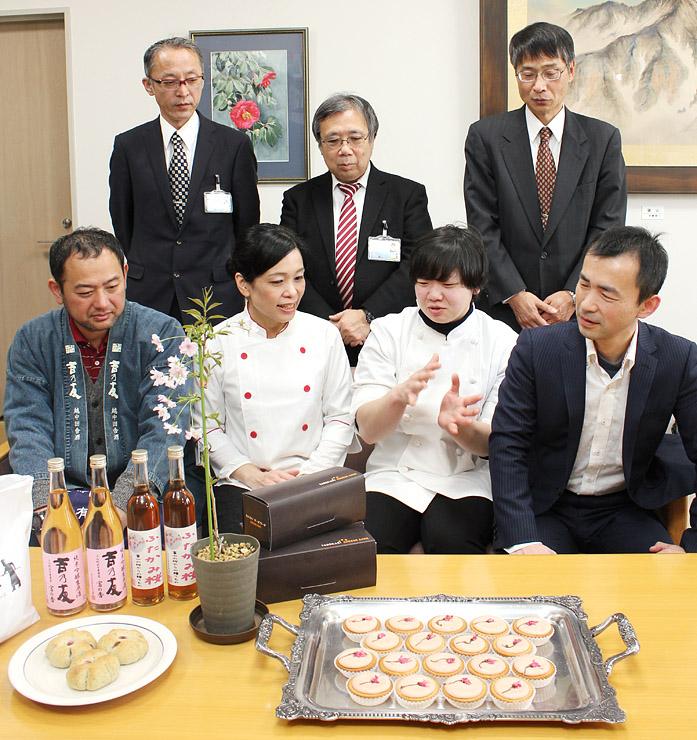 商品を前に、特徴などを話す大澤社長(前列右)ら出席者