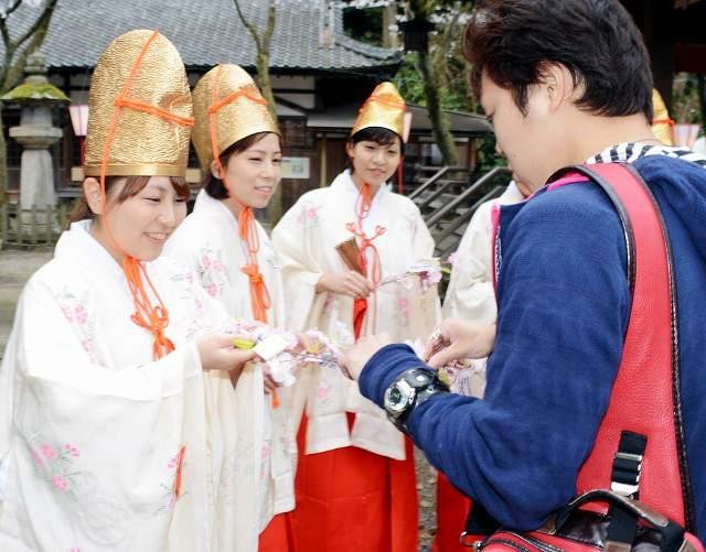 来場者と桜の小枝を交換する福娘たち=1日、福井県敦賀市の金崎宮