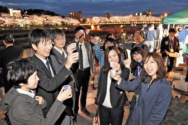 足羽川沿いのワインバーで地酒の振る舞いを楽しむ参加者=1日夜、福井市