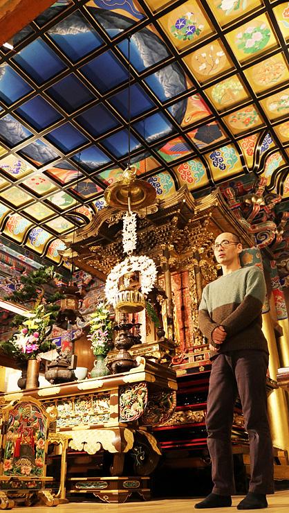 清河さんの天井画が描かれた本堂で2人展への期待を語る雪山さん=善巧寺
