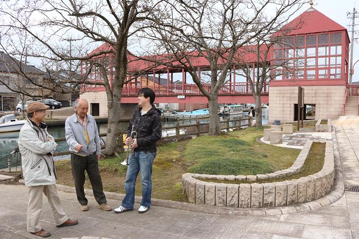 内川に架かる東橋近くの桜並木でライブの打ち合わせをする関係者=3月下旬