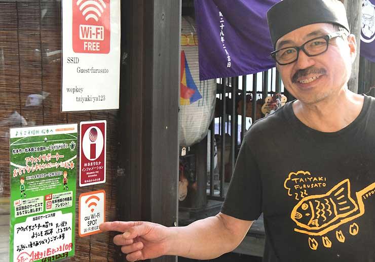 アウェーサポーター向けのサービス内容を書いた店頭のポスターを指さす山本さん