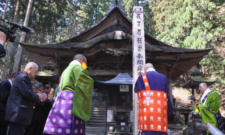 本堂前に立つ回向柱の前で手を合わせる吉沢住職(右から2人目)ら