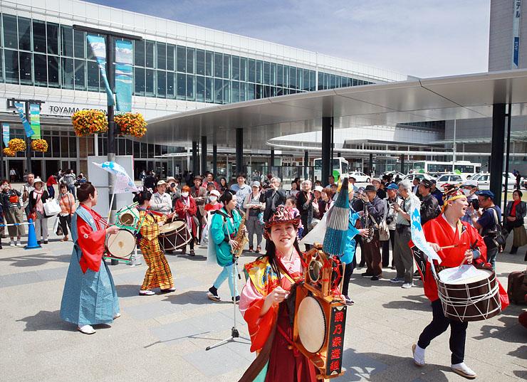 北陸新幹線が開業して1年のJR富山駅前で大勢の人たちを楽しませるチンドンのグループ=富山市明輪町