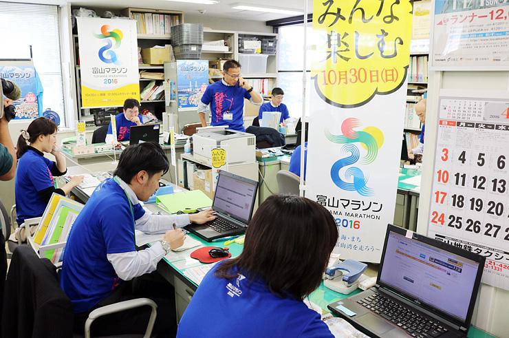 電話応対やパソコン画面のチェックに追われる事務局のスタッフ=県庁