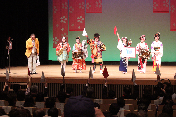 全日本チンドンコンクール本戦の決勝で審査の旗が上がる会場=県民会館
