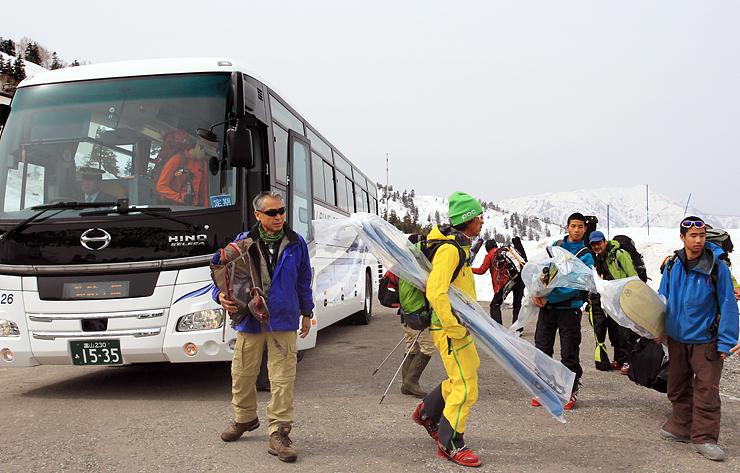 立山高原バスを降り、スキー板やスノーボードを手にする乗客=立山・弥陀ケ原