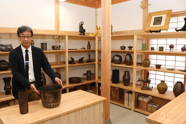 高岡銅器を並べ、オープンに向けて準備を進める竹中さん=高陵金寿堂