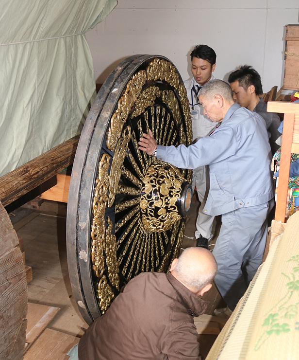 修復を終えて本体に取り付けられる小馬出町の車輪=高岡御車山収蔵庫