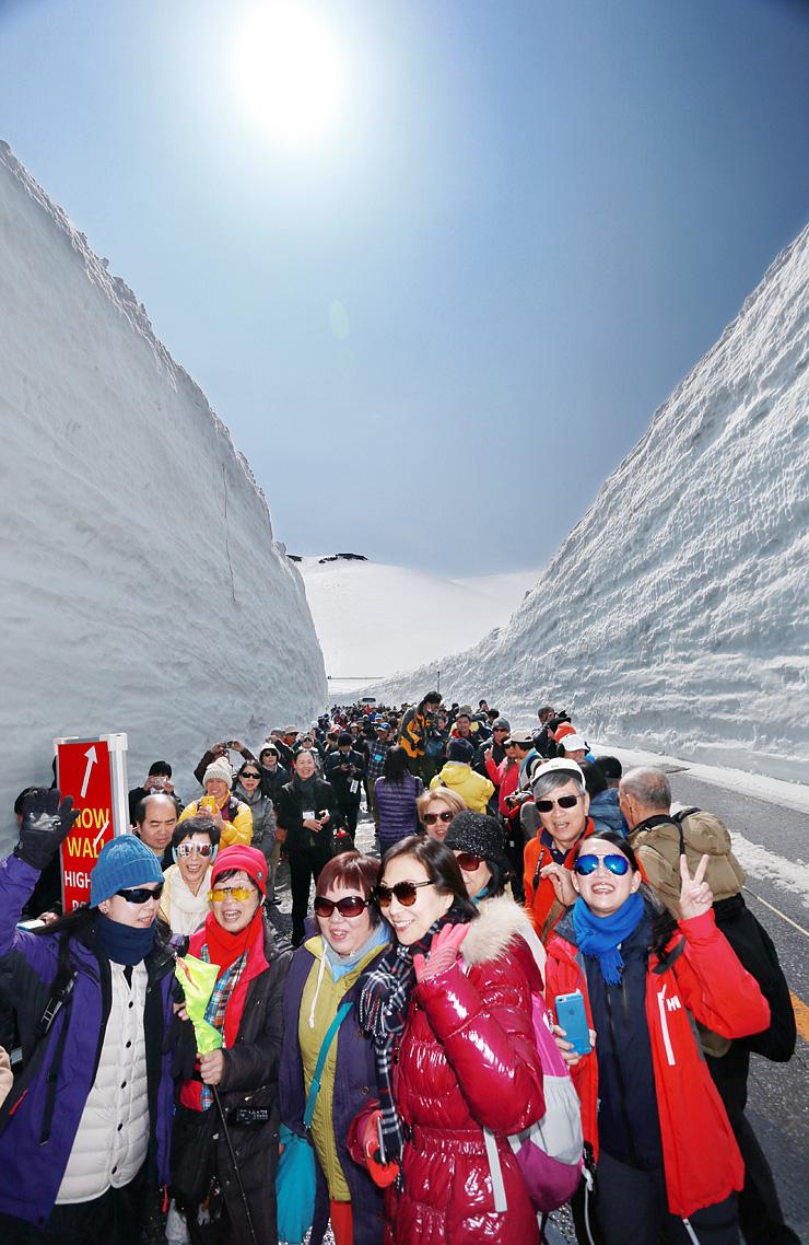 高さ13メートルの雪壁がそそり立つ「雪の大谷」を散策する大勢の観光客=立山・室堂