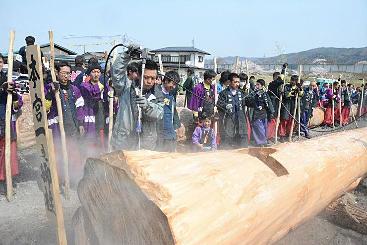 「本宮一」の御柱の皮をむき、高圧洗浄器で仕上げる氏子たち
