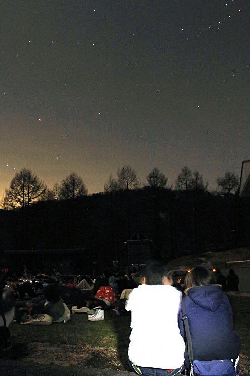 身を寄せ合って星空を眺めるツアー参加者ら=16日午後8時16分