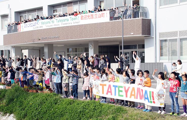近くの稚子塚駅を通過する列車に手を振る児童ら=立山北部小前