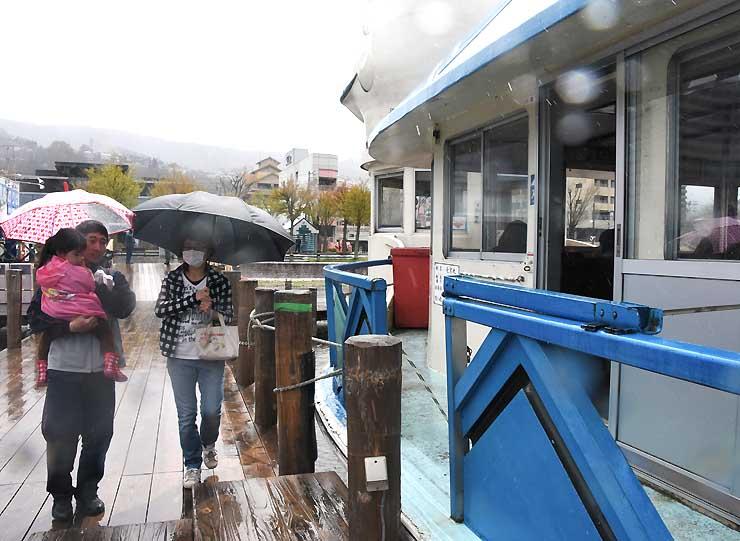 雨の中を無料となった遊覧船に乗り込む親子連れ
