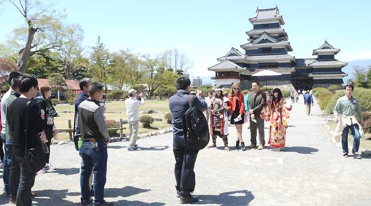 多くの外国人観光客でにぎわう松本城本丸庭園。写真撮影に応じる「松本城おもてなし隊」には希望者の列ができた=19日午前