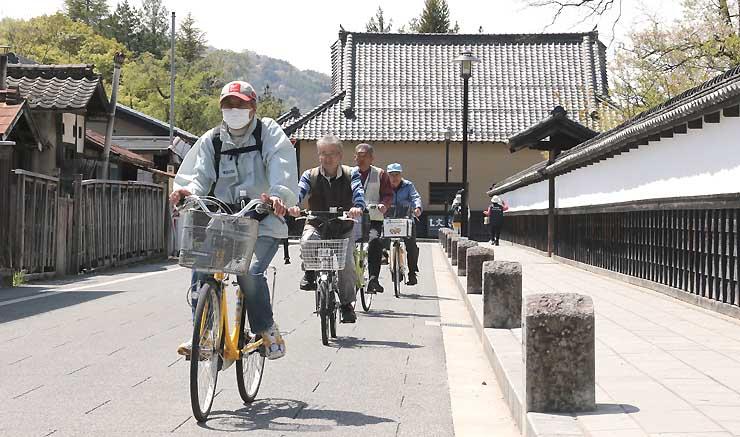 真田家ゆかりの史跡を巡りながら、松代地区内を自転車で散策する参加者たち=20日、長野市
