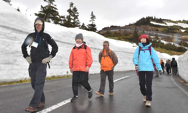 例年より低い雪の壁の間を歩く参加者たち=21日午後1時25分、群馬県の山田峠付近
