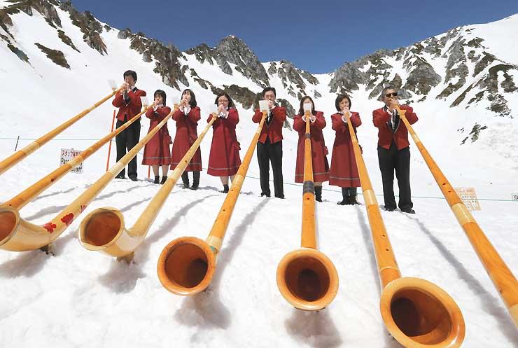 快晴の下、宝剣岳を背景にアルプホルンの演奏が響いた開山式=22日、中央アルプス千畳敷カール