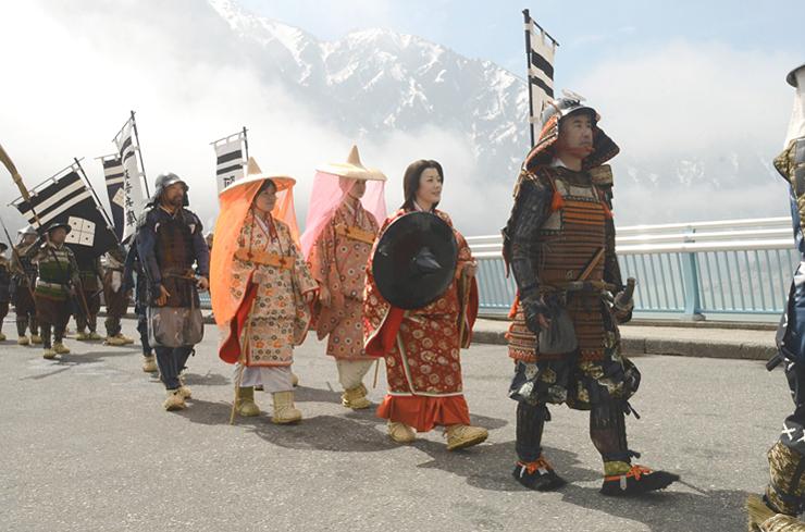 戦国武将や姫をイメージした衣装で黒部ダムの上を歩く武者行列