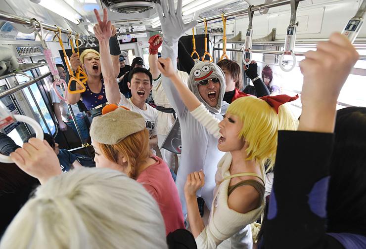 大音量のアニメソングが響く列車内で盛り上がる参加者たち