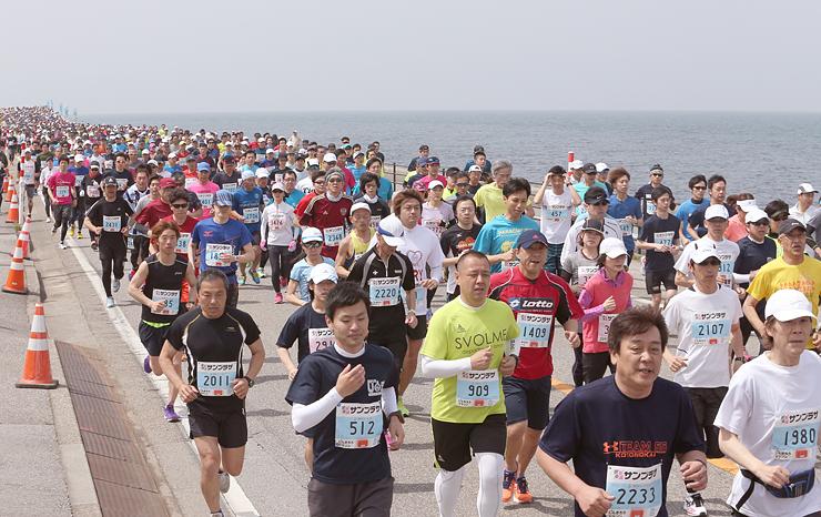 潮風を受けて海岸沿いのしんきろうロードを走る参加者=魚津市青島