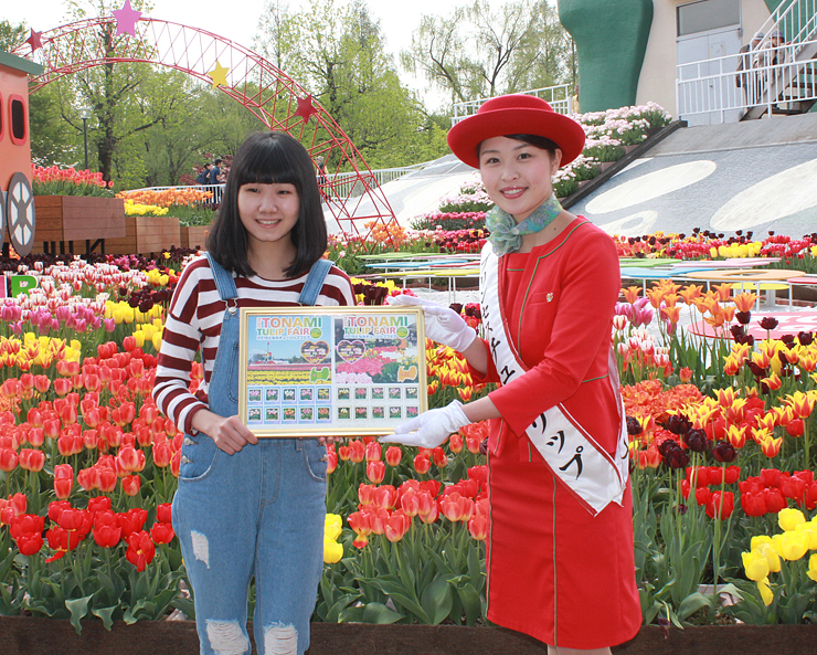 中筋さんから記念切手のシートを受け取る邱さん(左)