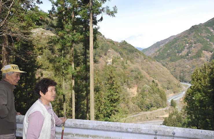 伐採した場所で景色を眺める山崎誠さん(左)と典子さん