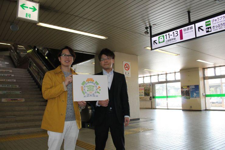 JR燕三条駅で開く直売所の看板を持つ武田修美さん(左)と結城靖博さん=三条市