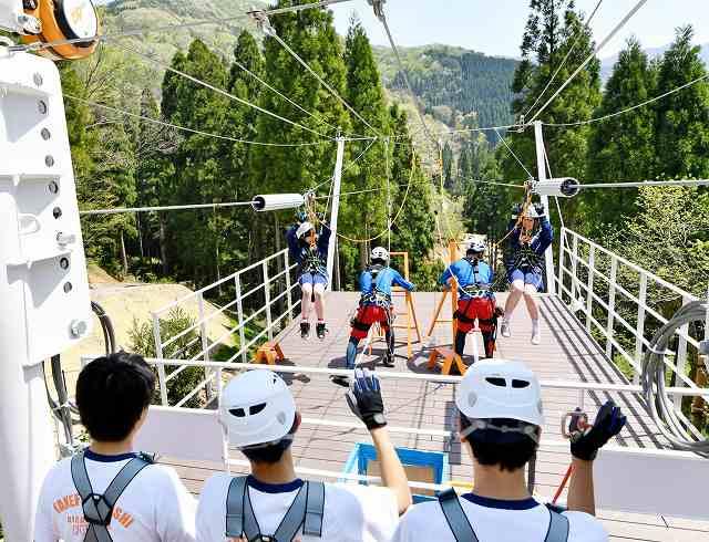 日本最長の往復1キロをワイヤケーブルで滑り降りる「メガジップライン」=26日、池田町志津原