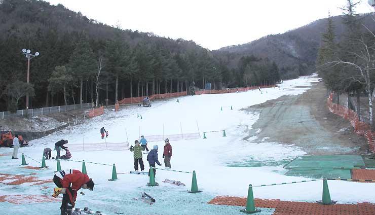 暖冬による雪不足でゲレンデの地肌が目立つ南信地方のスキー場=昨年12月27日