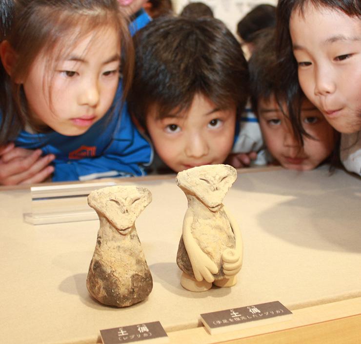 「ほほ笑みの土偶」を忠実に再現した複製品(左)。欠けた手と足を再現した複製品も作った