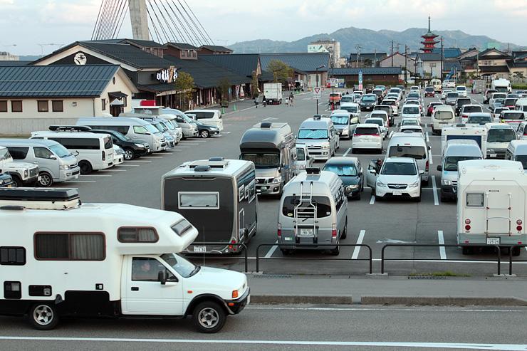 キャンピングカーが続々と訪れるひみ番屋街の駐車場=29日午後6時20分ごろ、氷見市北大町