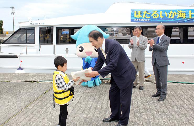 最初の乗船客となり上田市長から記念品を受ける高原君(左)=滑川漁港