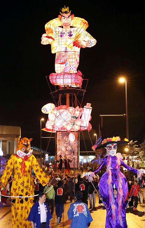 2体の巨大人形に先導され、引き回される文久の大行燈=JR福野駅前