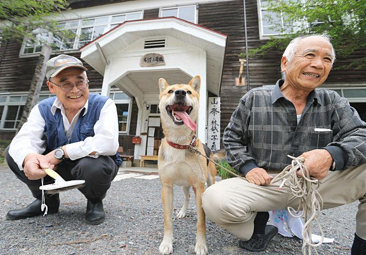 旧木沢小学校の「犬教頭」に着任したハッチ。世話をしている前沢さん(左)や山崎さんらが優しく見守っている